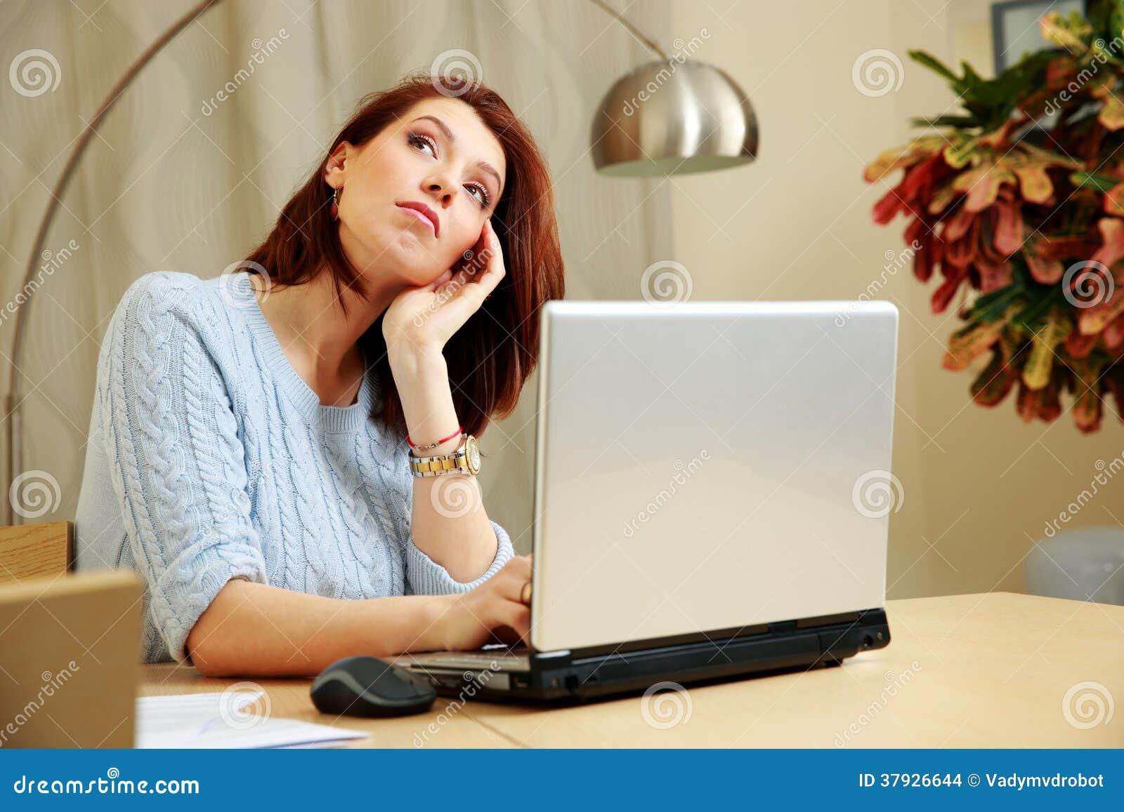 Задумчивая женщина сидя на ее рабочем месте