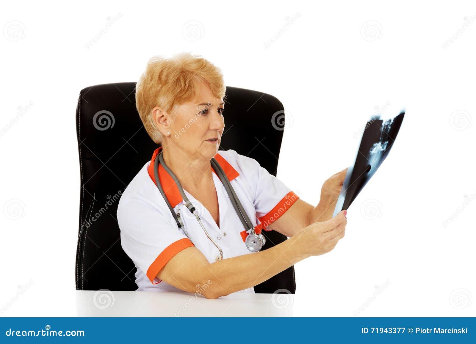 Задумчивый пожилой женский доктор ища фото рентгеновского снимка