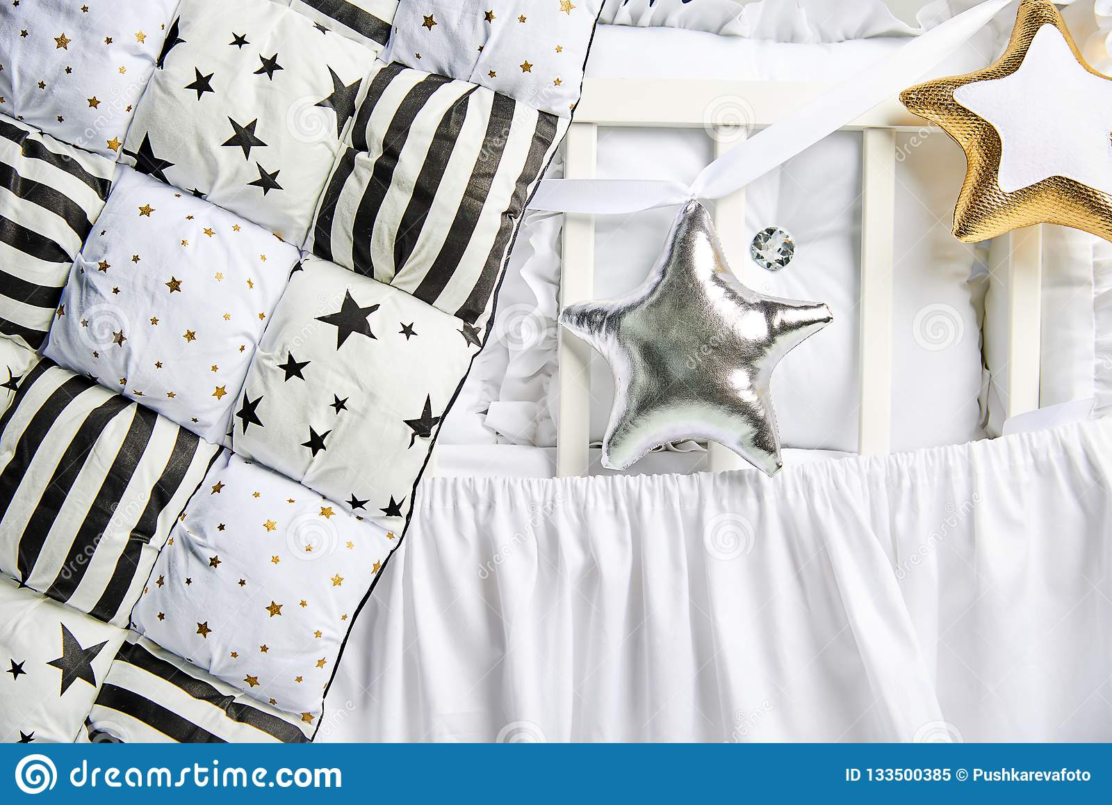Звезда серебра и золота сформировала подушки и одеяло заплатки на белой кроватке младенца