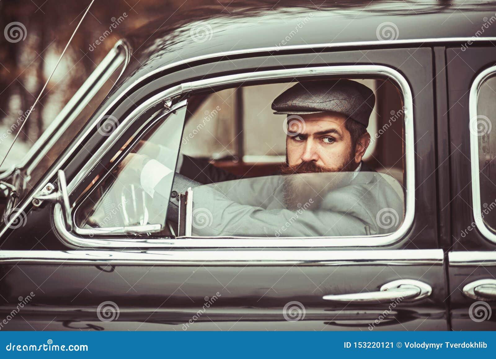 Зверский бородатый человек с усиком внутри с темными волосами и длинной бородой в ретро автомобиле
