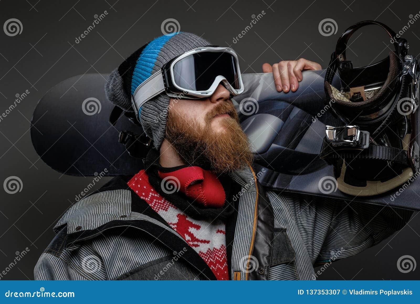 Зверский человек с красной бородой нося полное удерживание оборудования сноуборд на его плече, изолированном на темной предпосылк