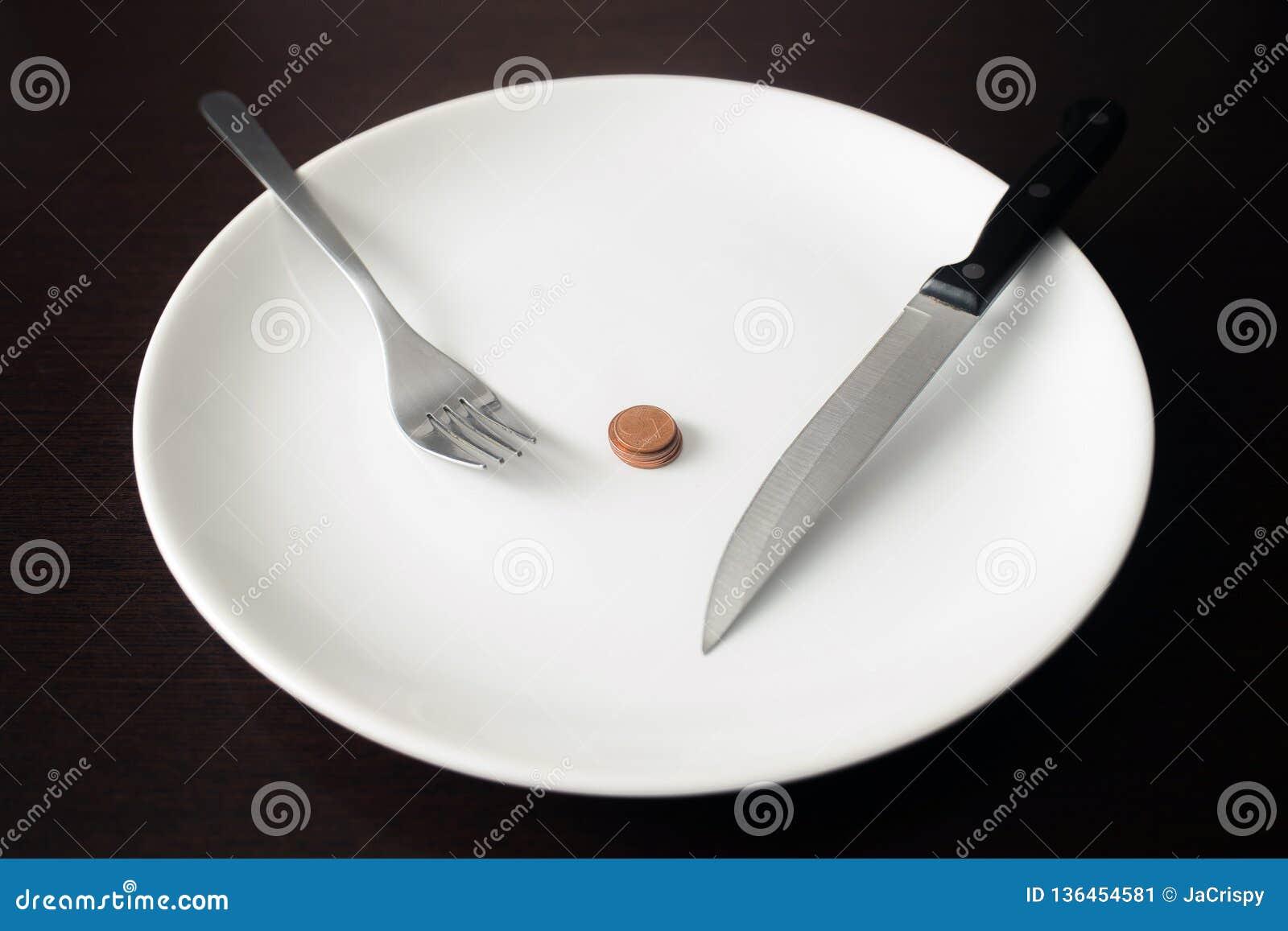 Здоровая еда, бедность, сохраняя деньги: монетки на белой плите на столовой