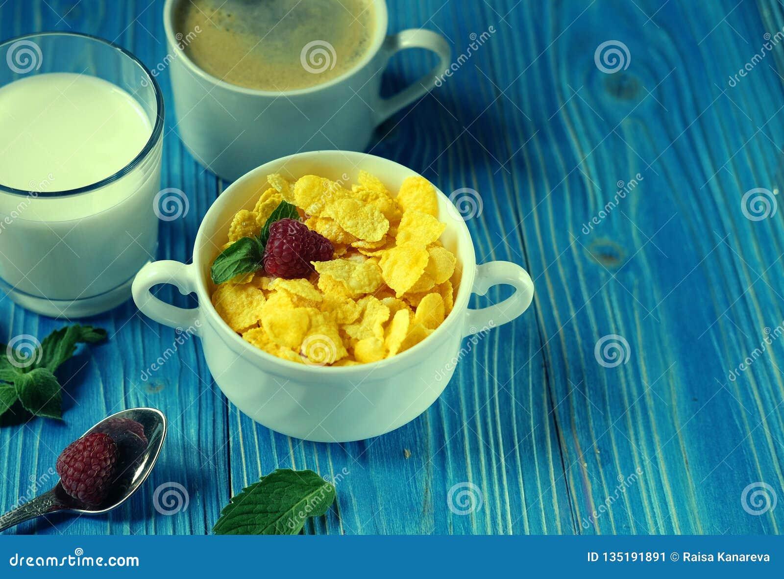 Здоровая еда, еда и концепция диеты - корнфлексы с ягодами, молоком и кофе для предпосылки завтрака голубой деревянной