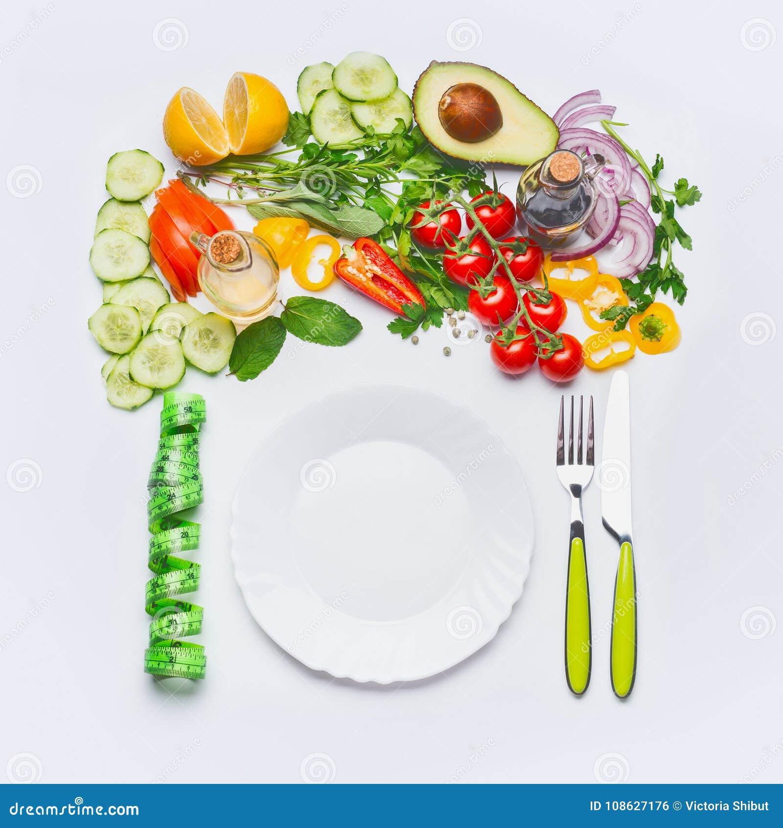 Здоровая чистая концепция еды еды или диеты Различные овощи салата с белой плитой, столовым прибором и зеленой измеряя лентой