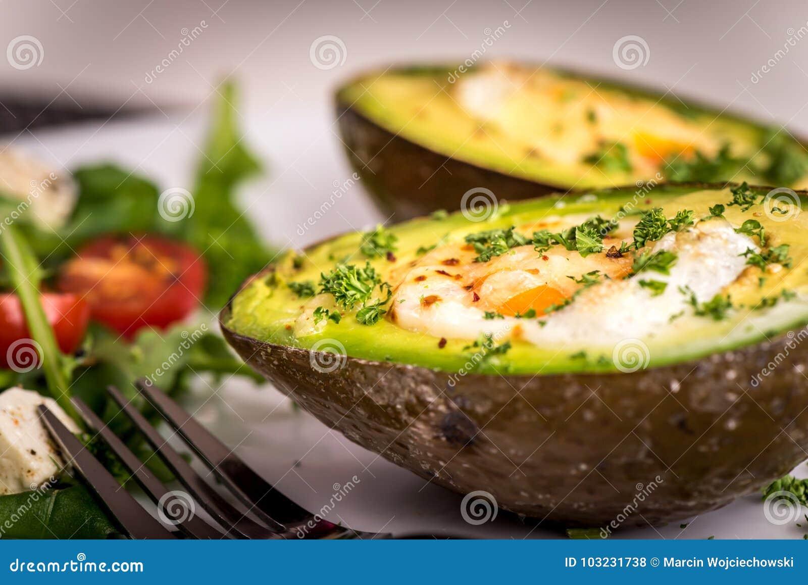 Здоровое блюдо vegan - авокадо испек с яичком и салатом с rucola