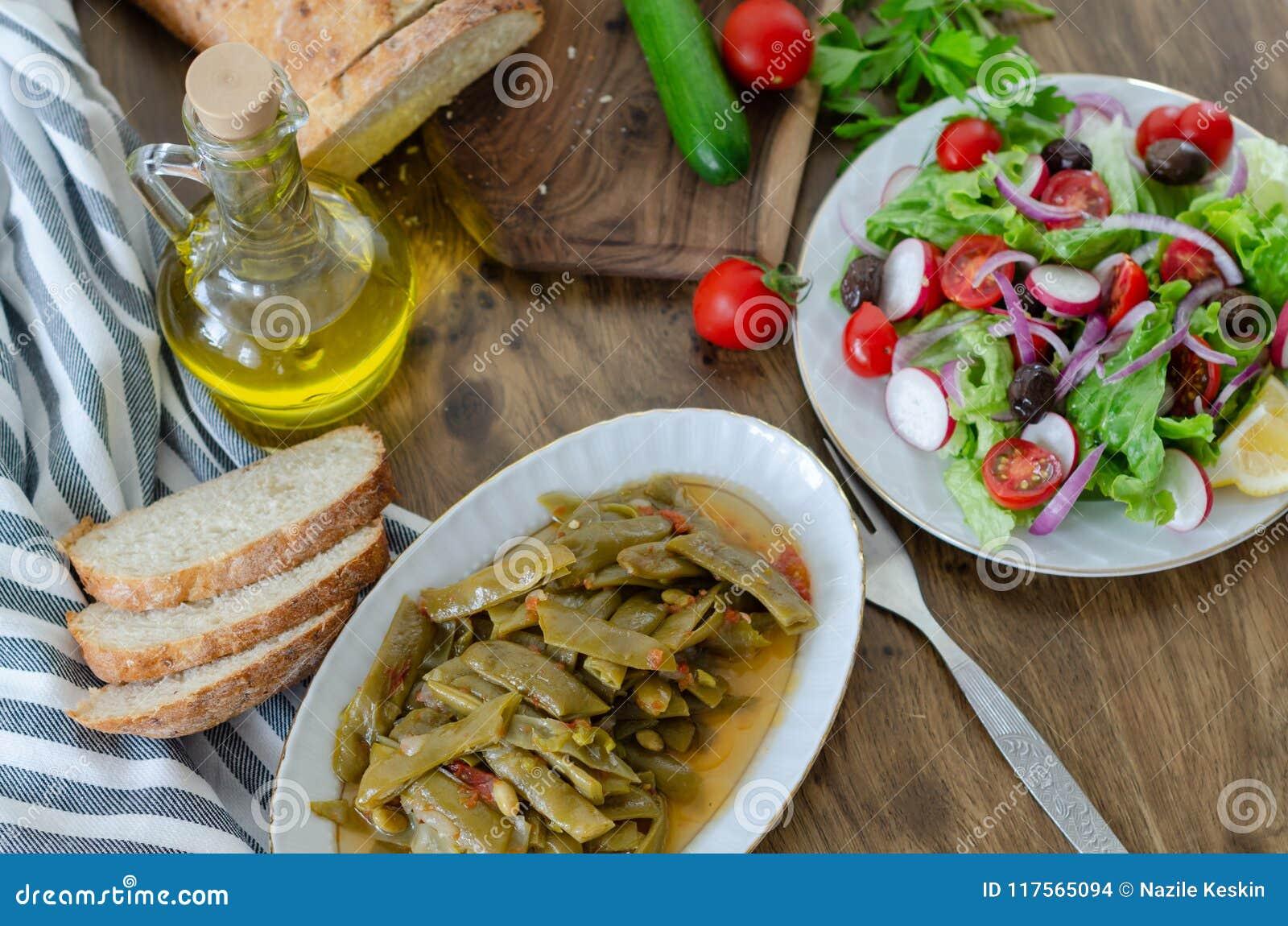 Здоровые привычки еды, оливковое масло с едой фасоли и салат и