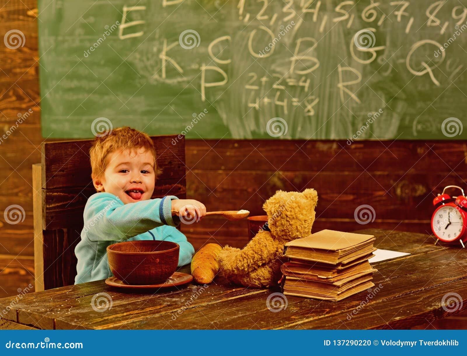 Здоровый обед в школьном кафетерии Обед доли маленького ребенка здоровый с другом игрушки Мальчик наслаждается здоровым обедом с