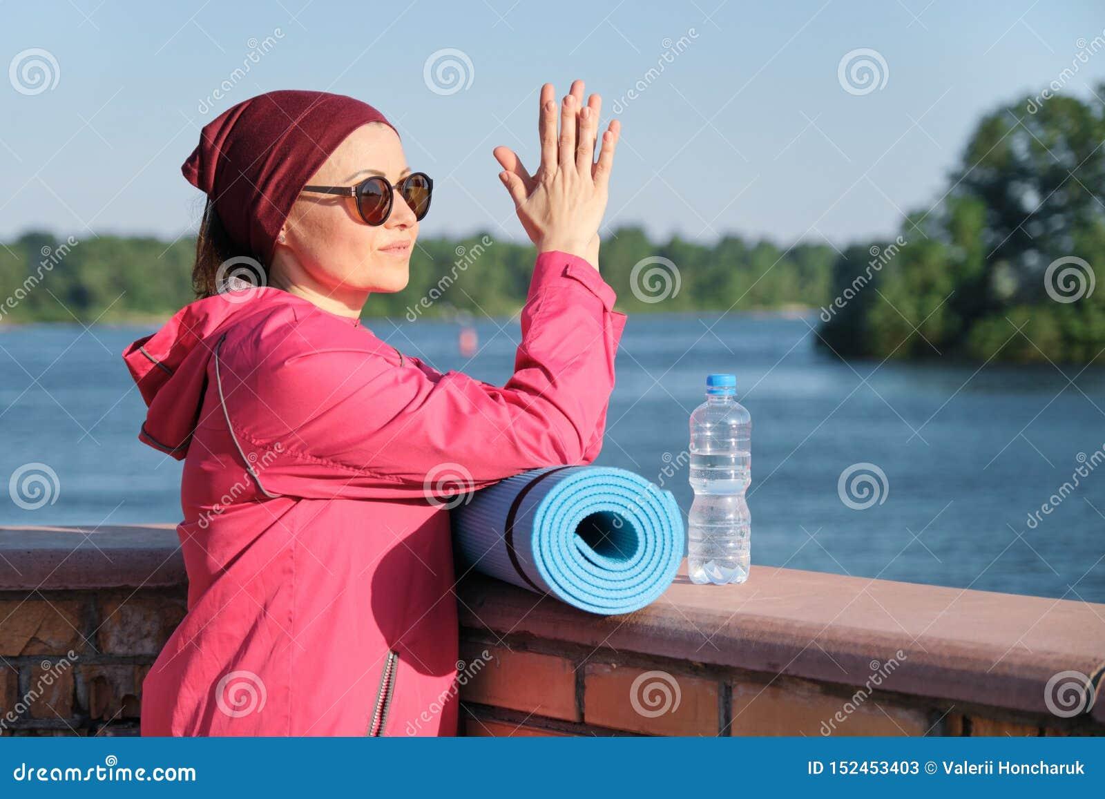 Здоровый образ жизни зрелой женщины, на открытом воздухе портрета женщины возраста в sportswear с циновкой йоги и бутылки воды