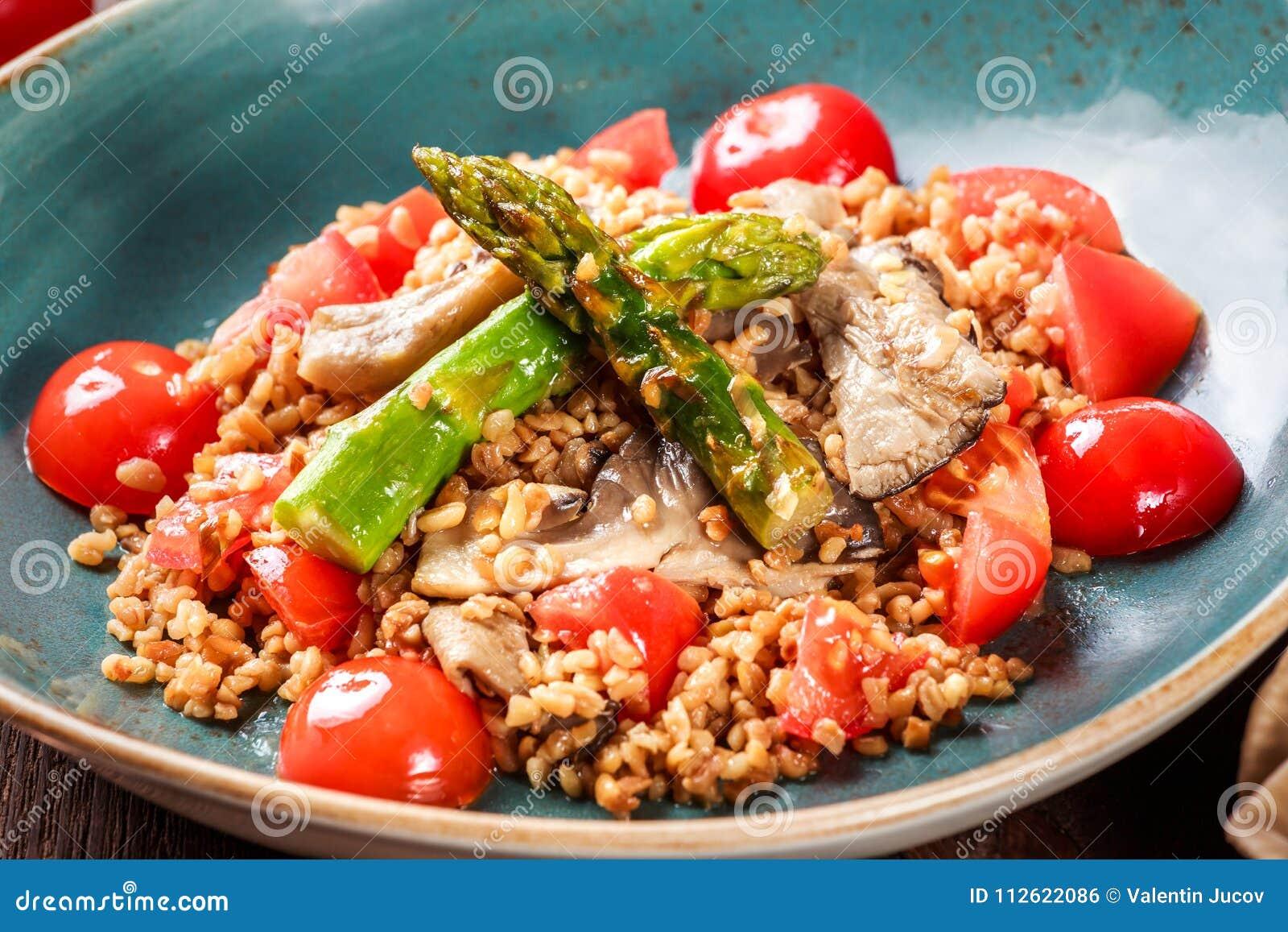 Здоровый салат каши ячменя с спаржей, томатами и грибами на плите Еда Vegan