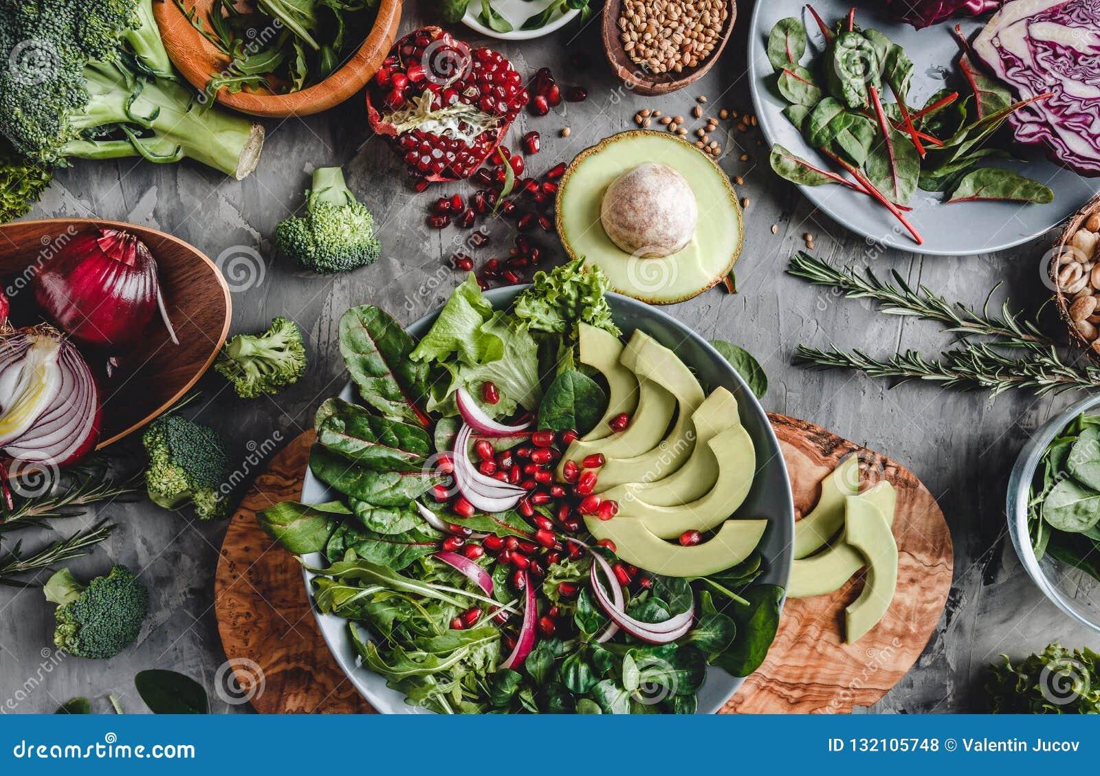 Здоровый свежий салат с авокадоом, зелеными цветами, arugula, шпинатом, гранатовым деревом в плите над серой предпосылкой Здорова