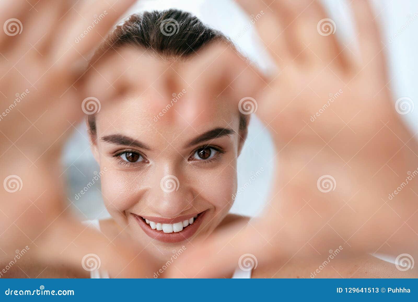 Здоровье глаза Красивая сторона женщины с руками сердца форменными бобра