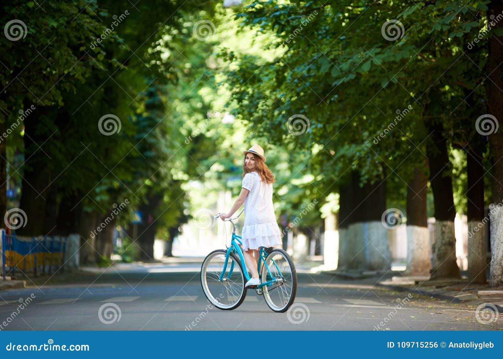 Зеленая городская посадка Езды женщины на велосипеде самостоятельно на дороге