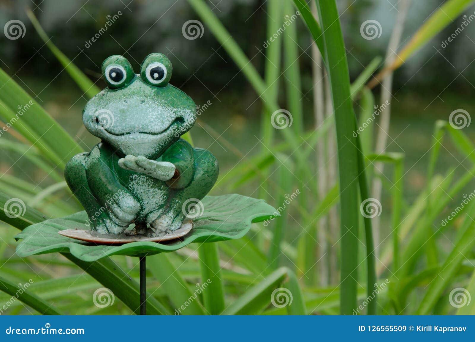 Зеленая лягушка игрушки на предпосылке травы