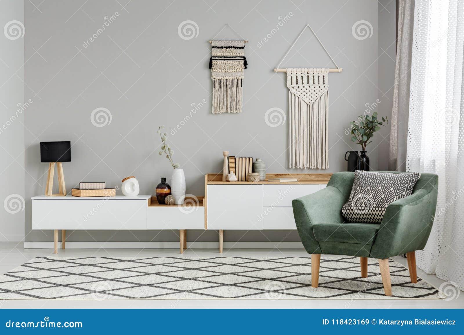 Зеленое кресло на сделанном по образцу ковре в ярком interio живущей комнаты