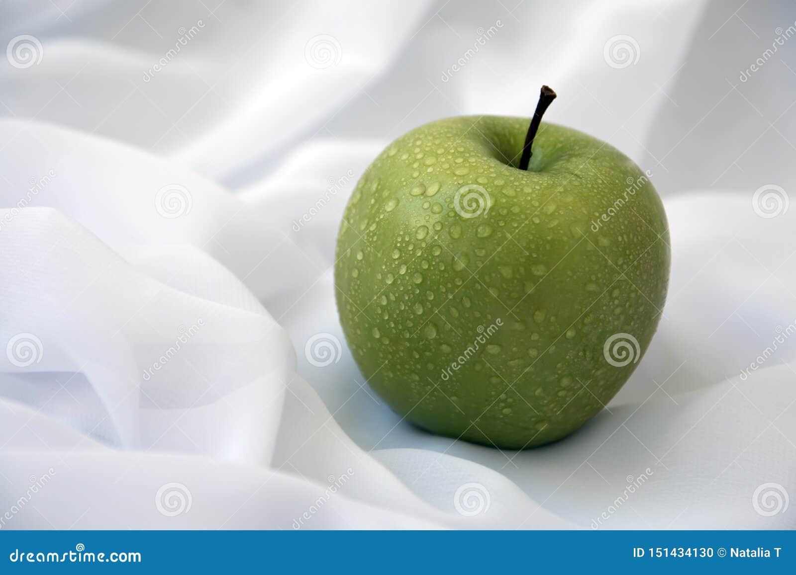 Зеленое яблоко на белой предпосылке, с капельками воды