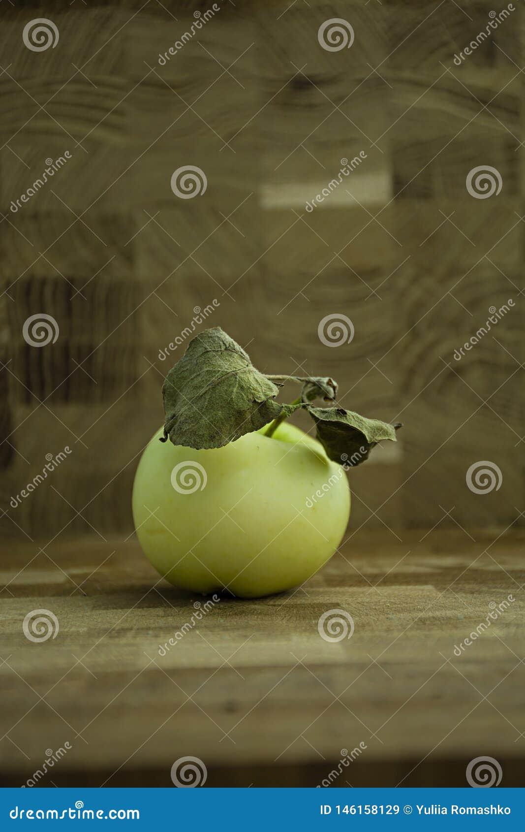 Зеленое яблоко на деревянной предпосылке