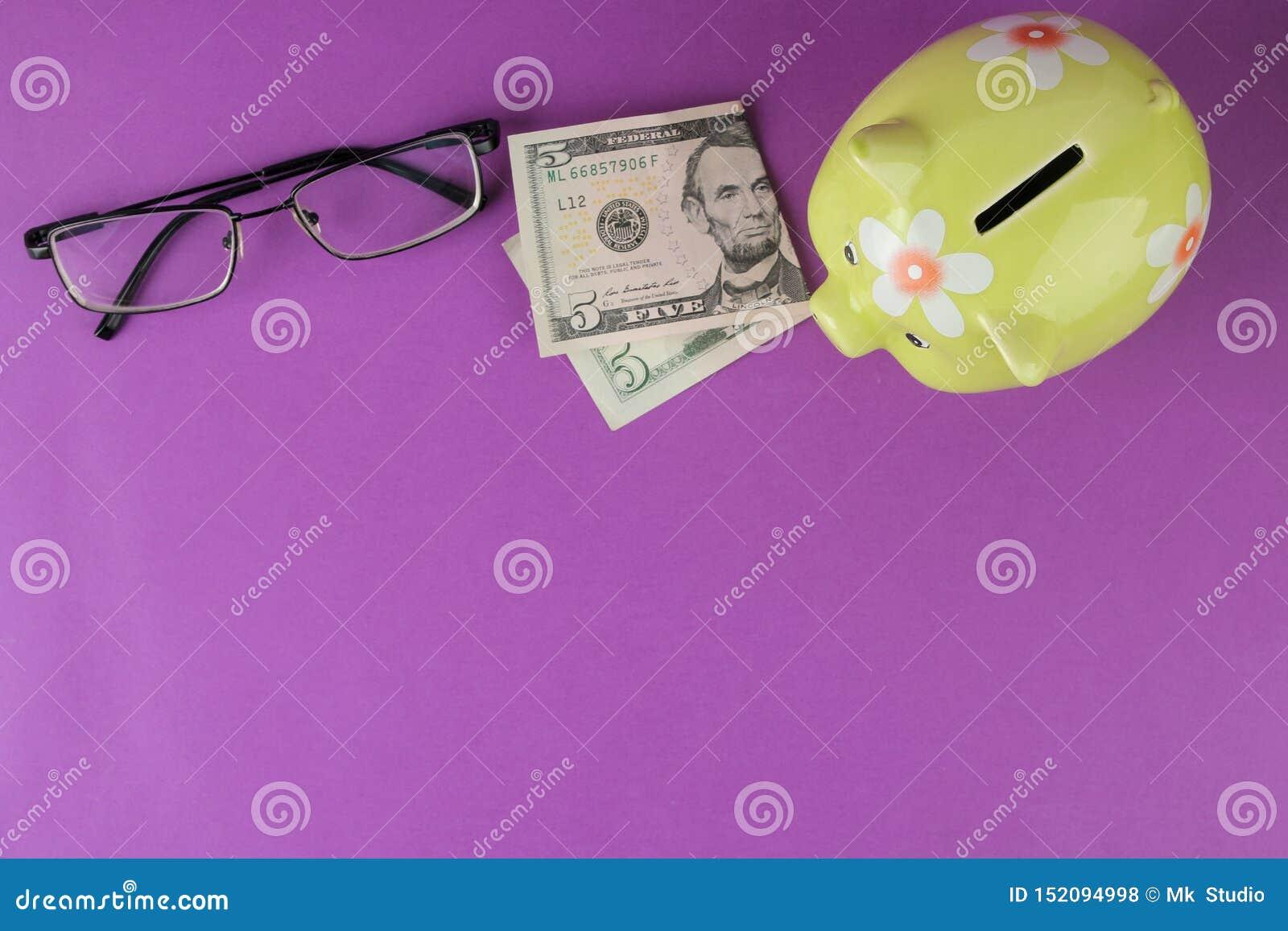Зеленые копилка и деньги и стекла на яркой пурпурной предпосылке Финансы, сбережения, деньги E r