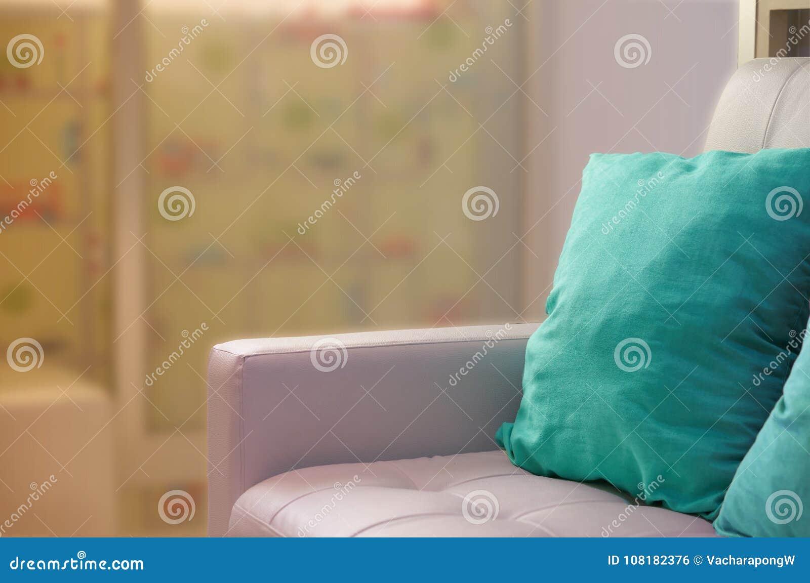 Зеленые подушки на белой софе около стеклянной двери