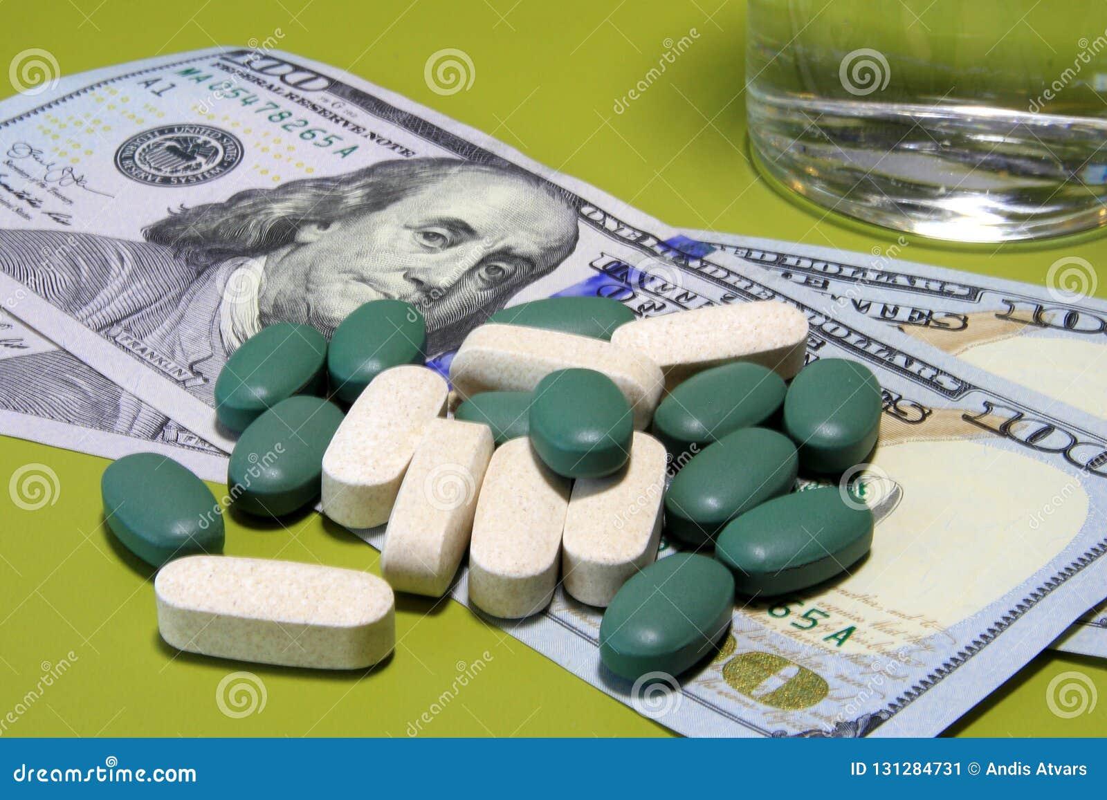 Зеленые таблетки разбросали на 100 долларовые банкноты Цена здоровой концепции жизни