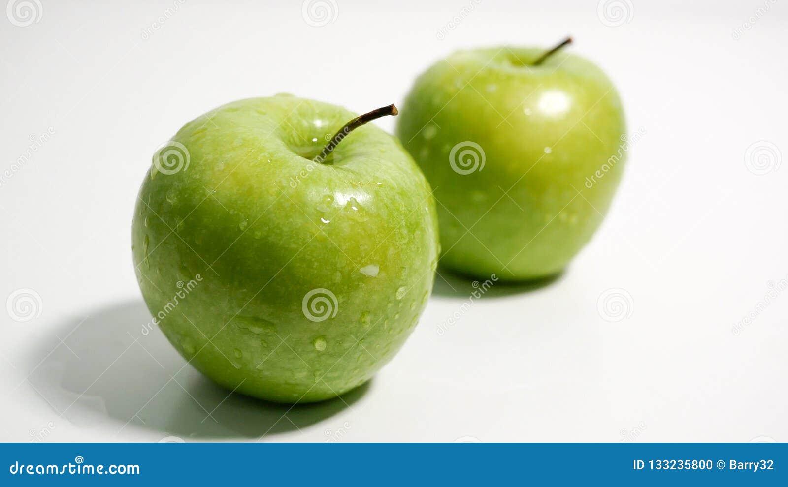 Зеленые яблоки с капельками воды на белой предпосылке