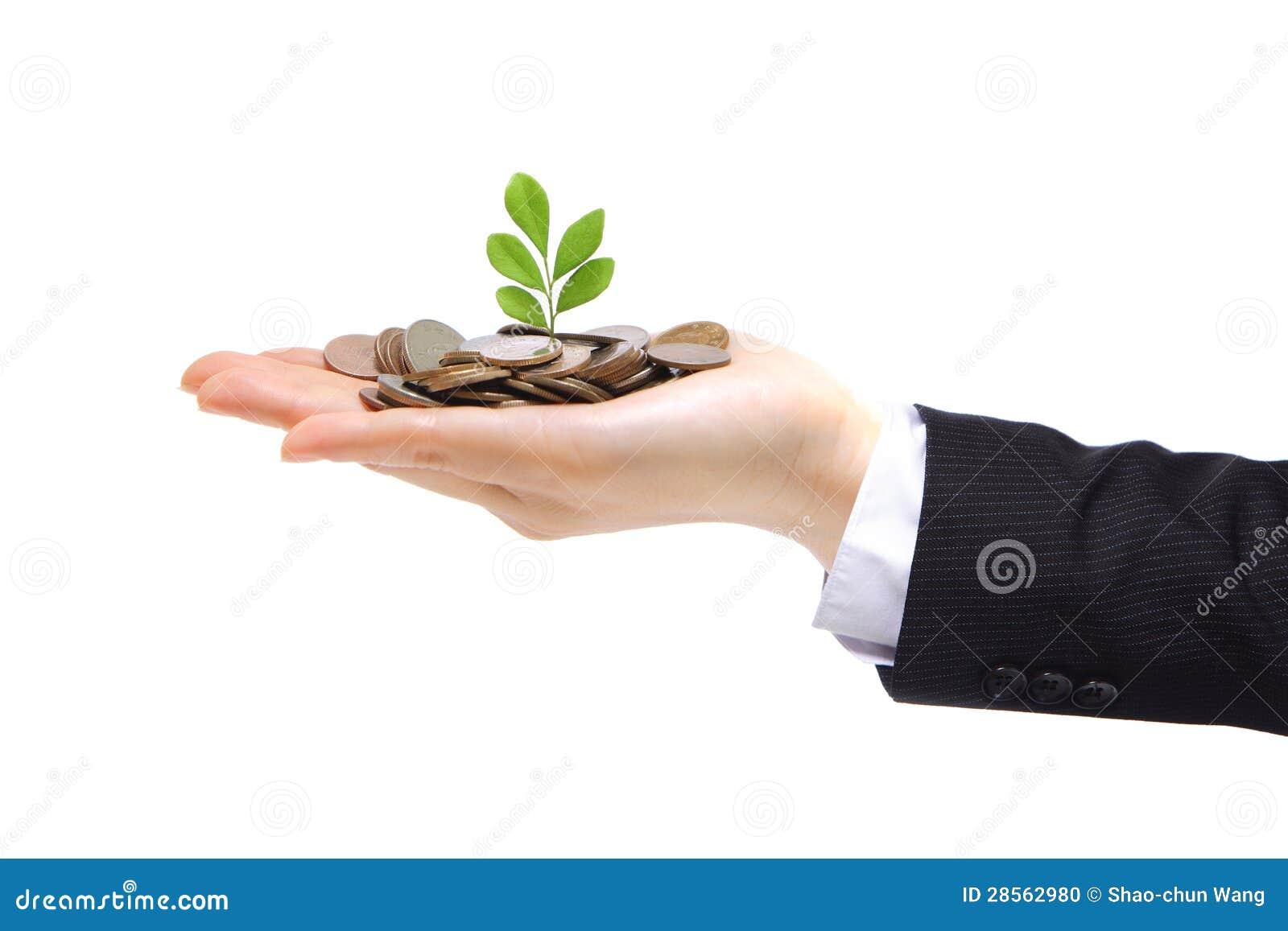 Зеленый завод пуская ростии от руки с деньгами