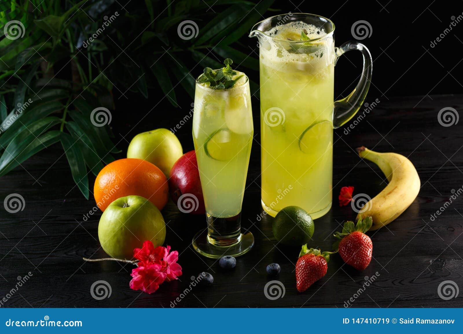 Зеленый лимонад яблока с известкой в кувшине и стекле и плодах на темной предпосылке