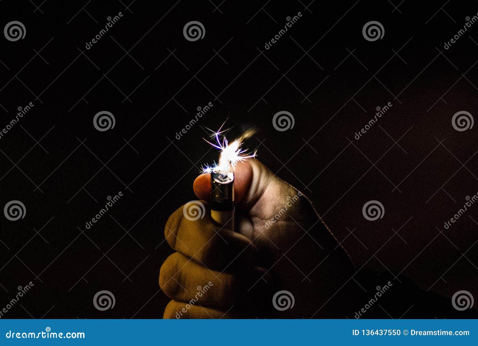 Зернистое изображение руки держа лихтер в ночи делая искру
