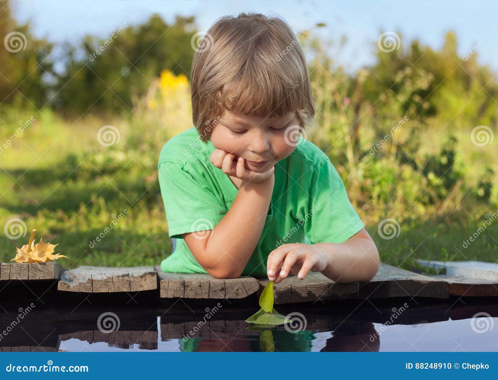 Зеленый лист-корабль в руке детей в воде, мальчике в игре парка с