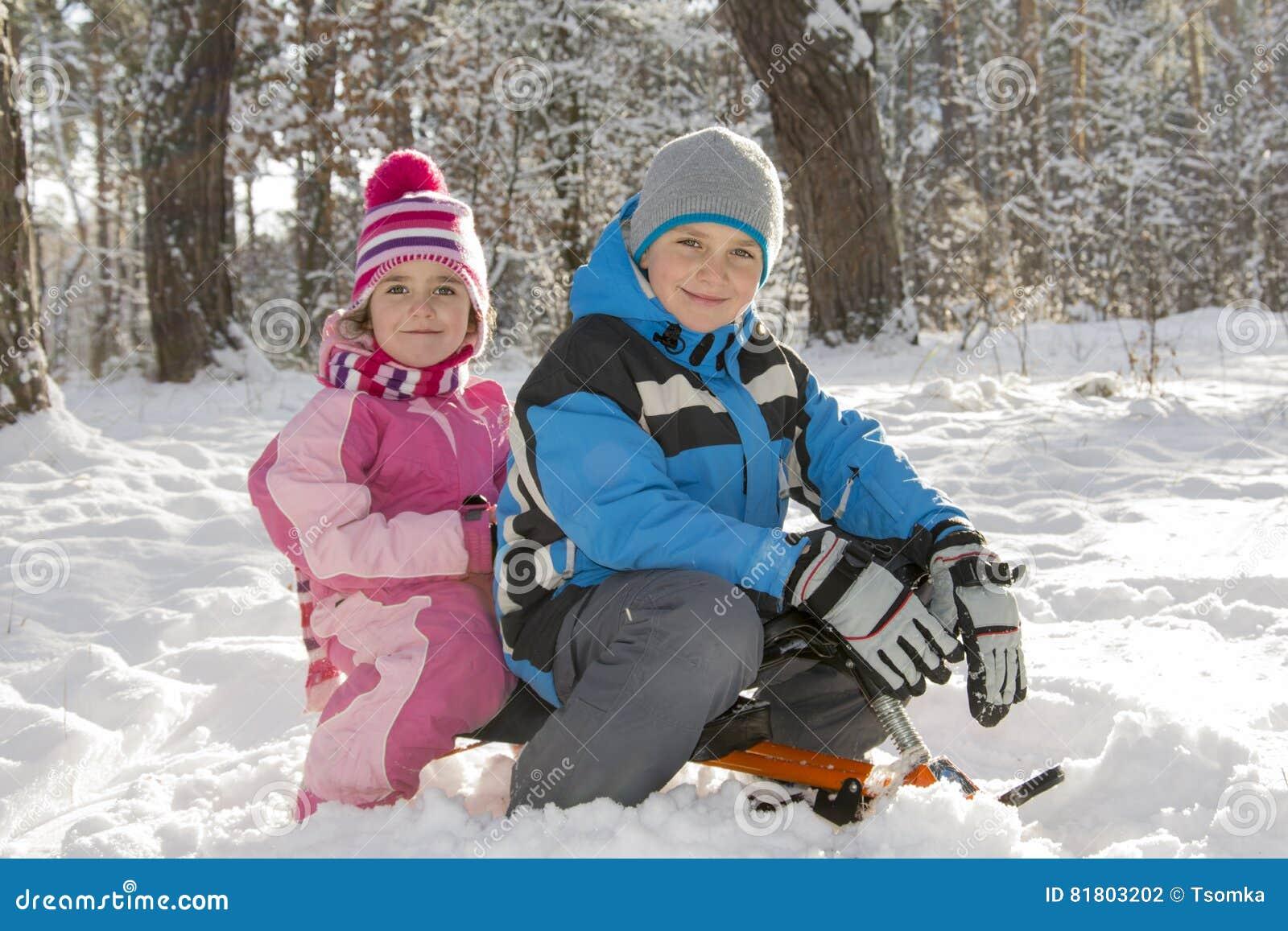 Зима в древесинах мальчик и девушка сидя на скелетоне