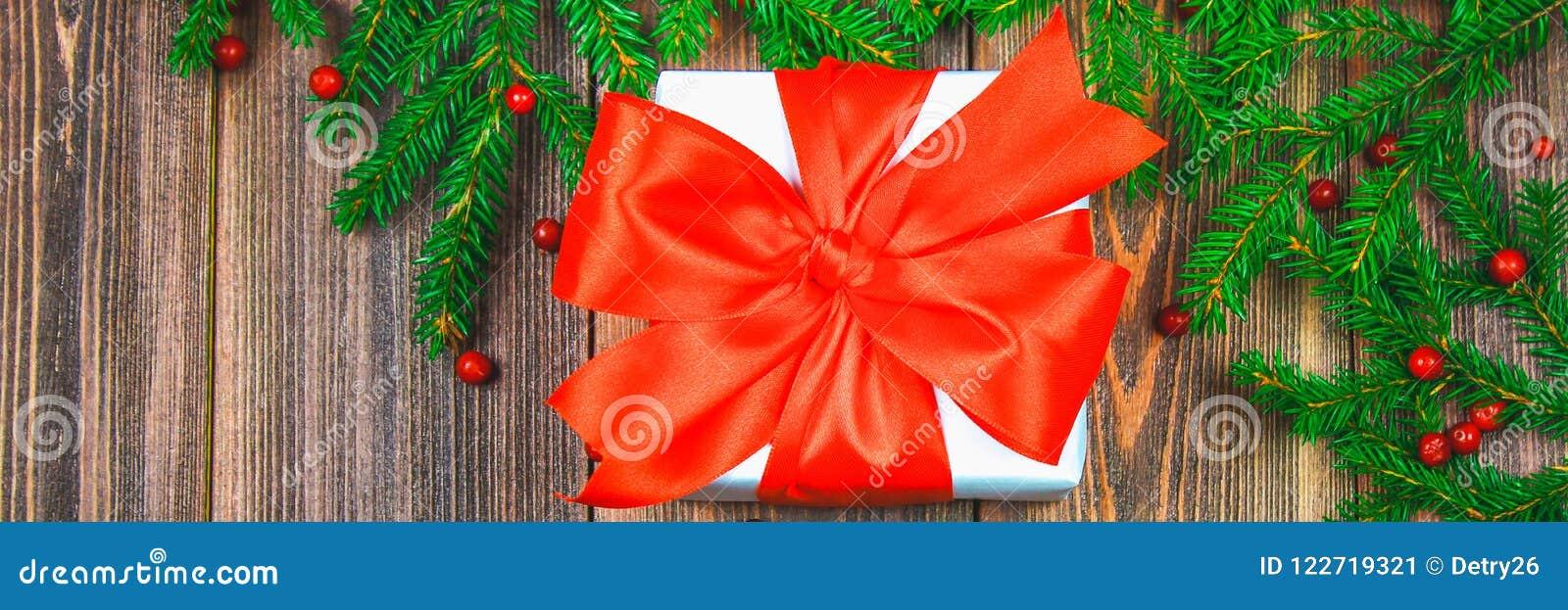 знамена Елевые ветви с красными ягодами на деревянном столе В центре коробки с настоящими моментами перевязанные смычки Рождество