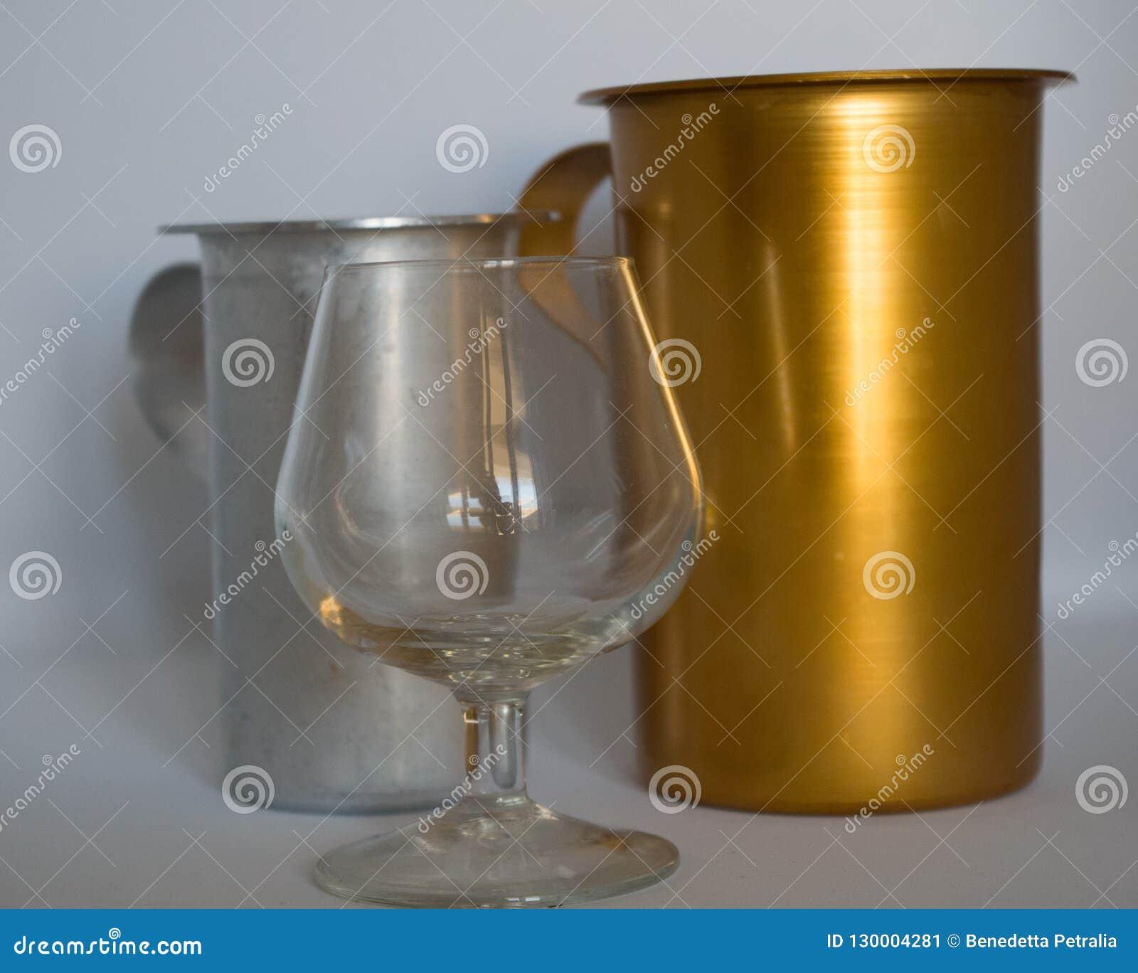 Золотой и серебристый кувшин со стеклом коньяка пустым на белой предпосылке