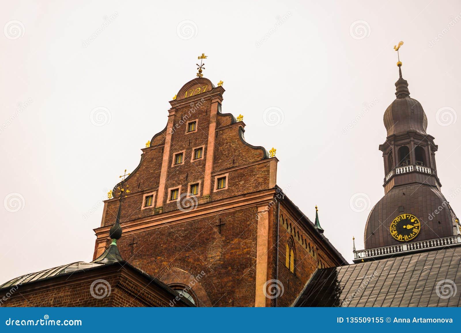 Золотой петушок на башне с часами Собор Риги на квадрате купола в историческом центре в старом городке Риги, Латвии