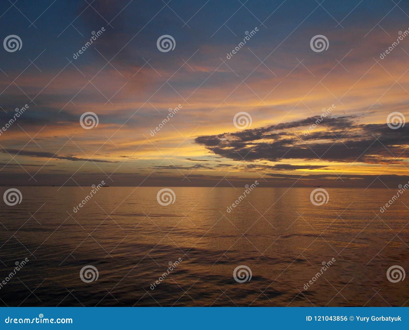 Золотой рассвет золота восхода солнца над поверхностью моря ровной