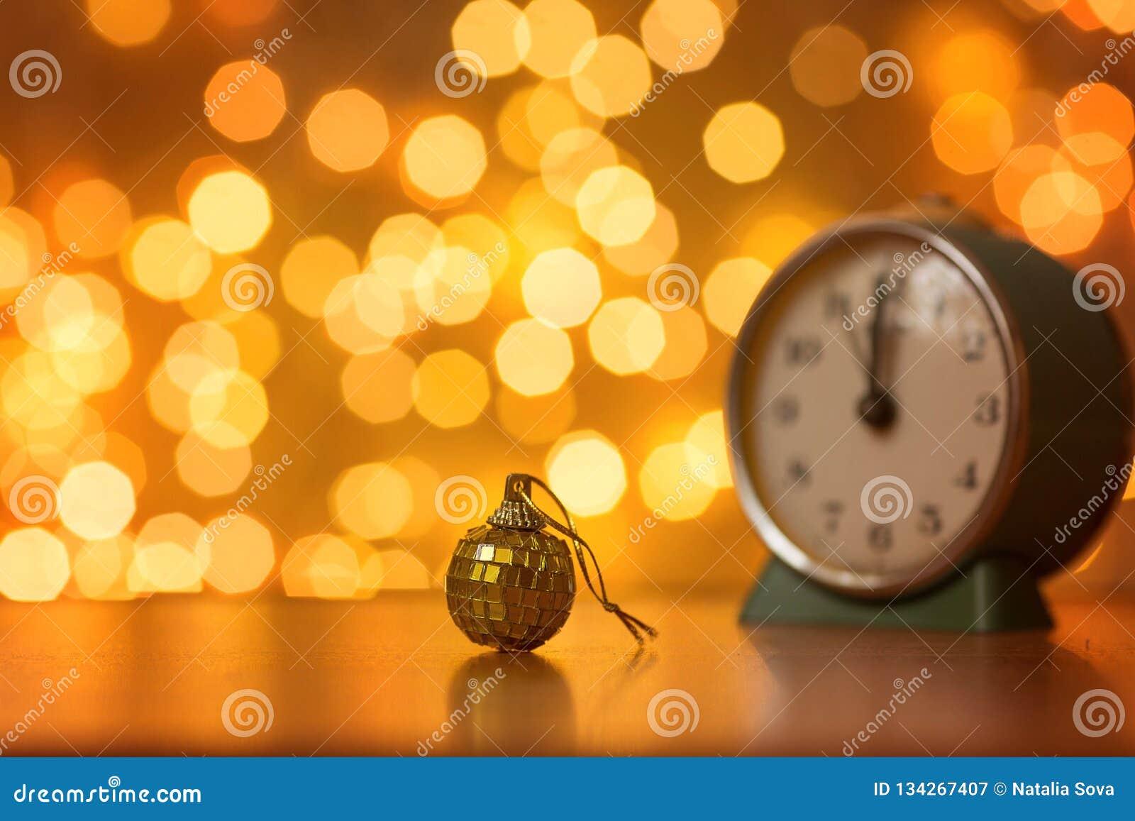Золотые шарик и часы на предпосылке расплывчатых светов