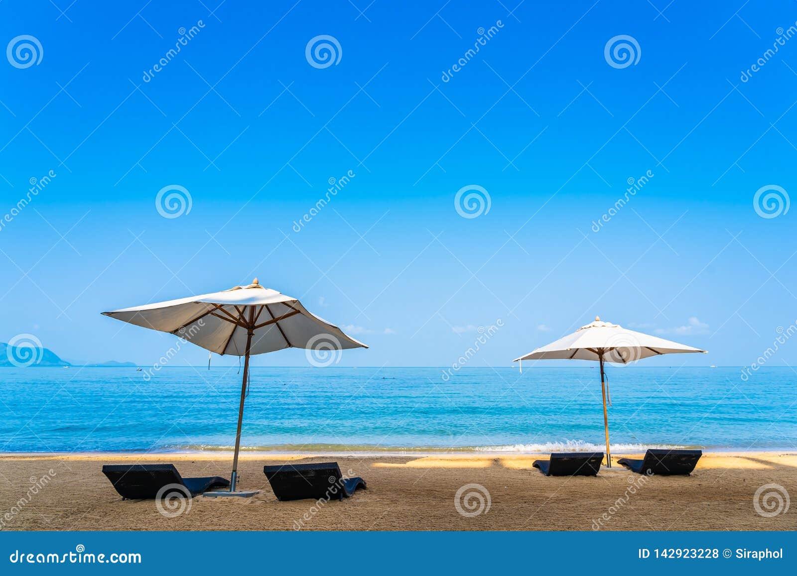 Зонтик и гостиная стула на красивом океане моря пляжа на небе