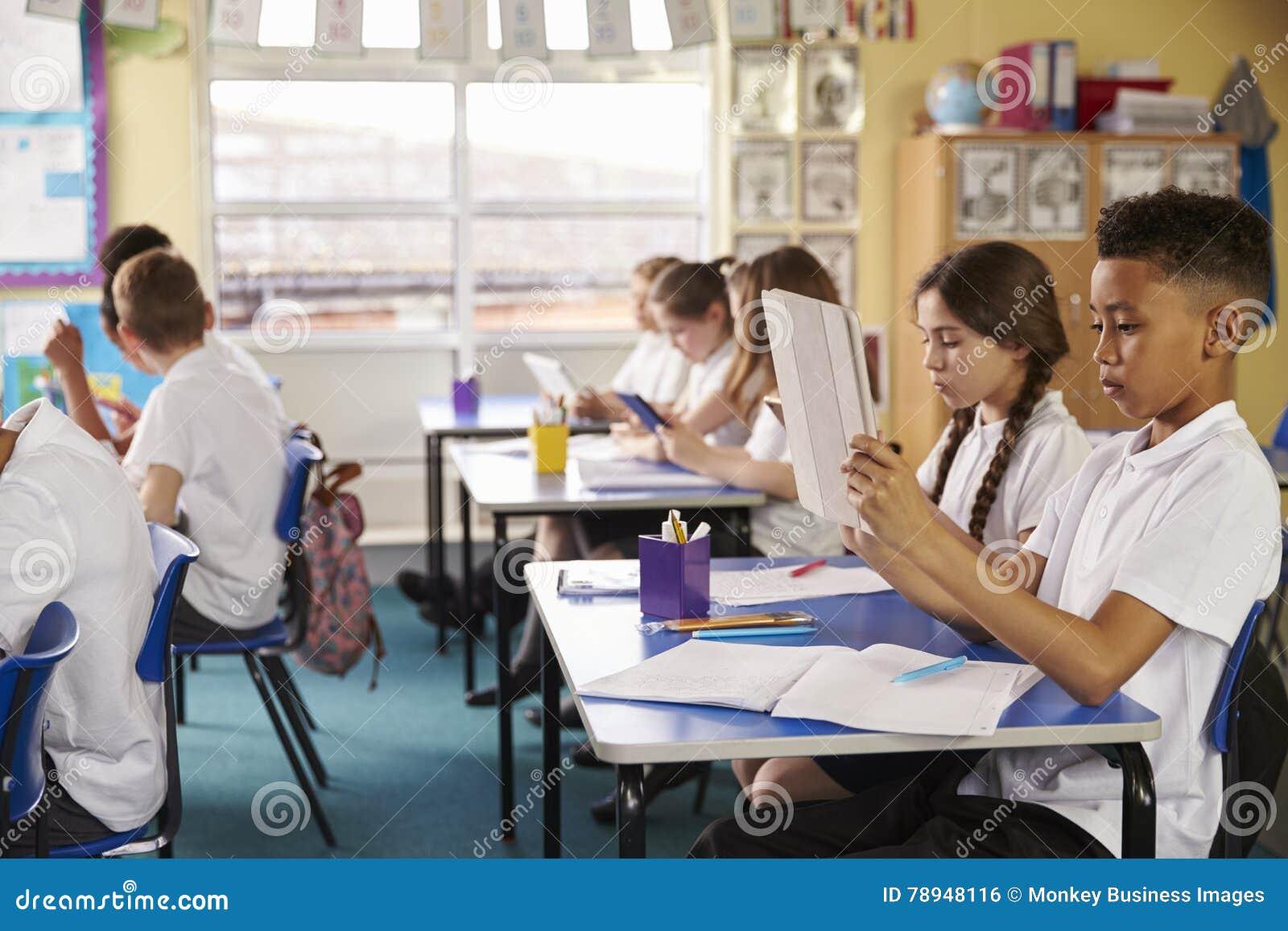 Зрачки используя планшеты в классе на начальной школе