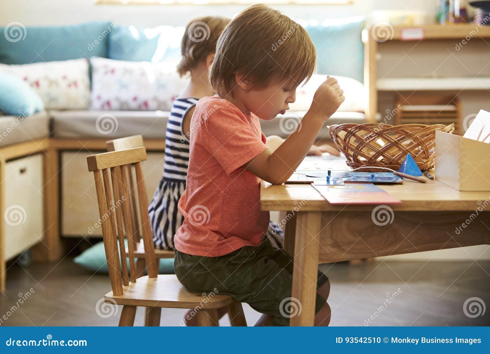 Зрачок Montessori работая на столе с деревянными формами