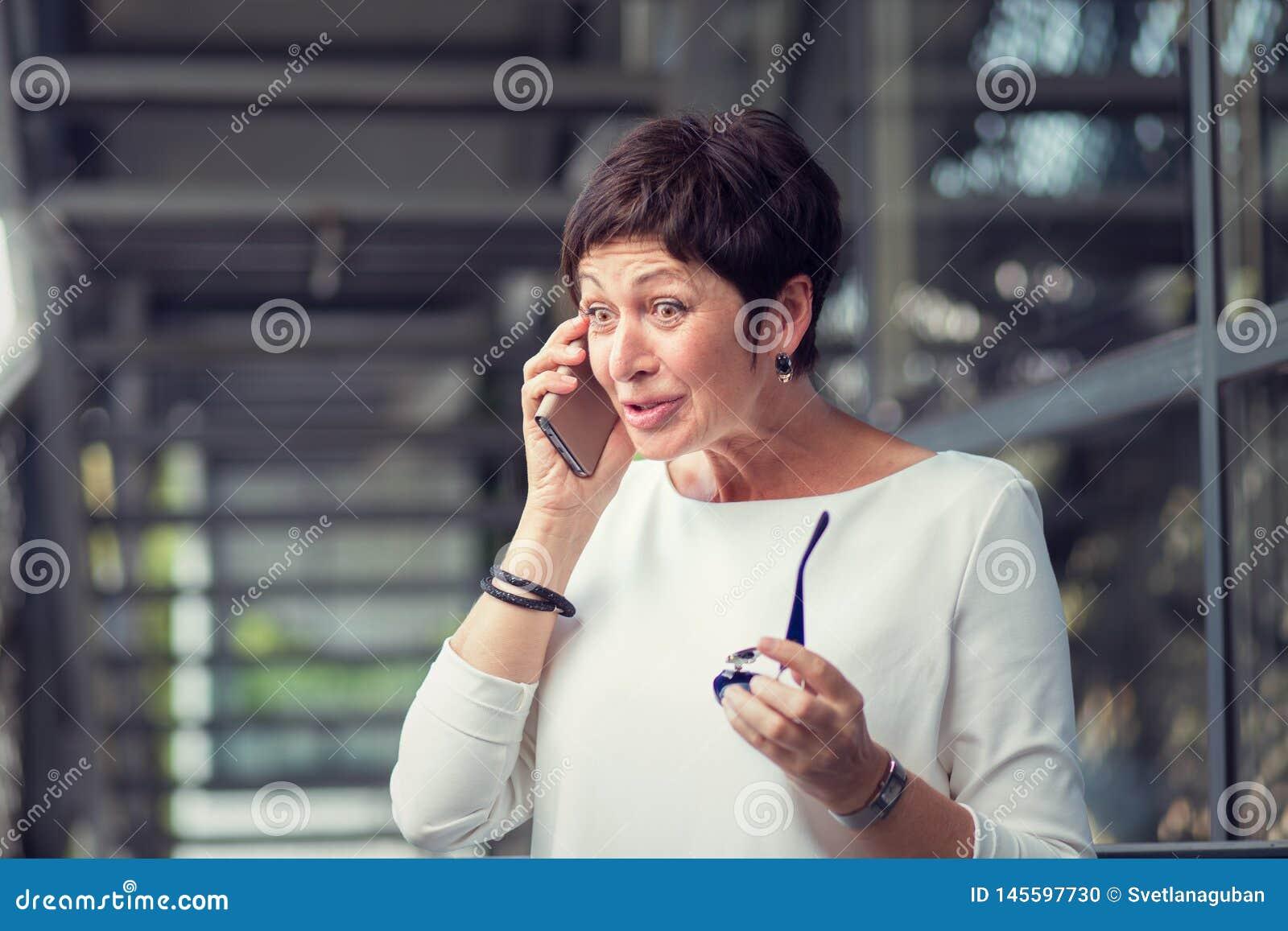 Зрелая женщина говоря на мобильном телефоне оглушенном чего она слышит