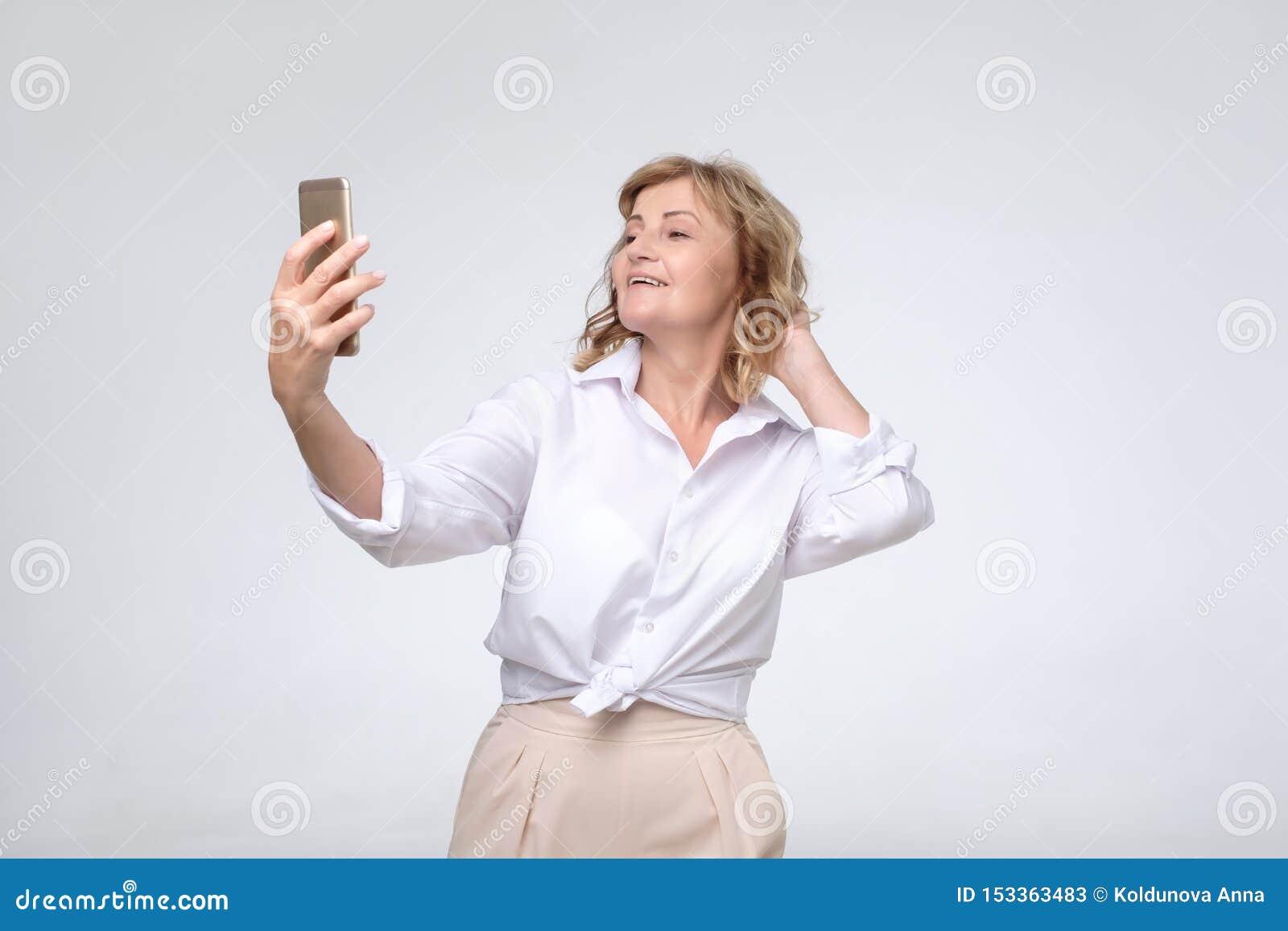 Зрелая милая женщина в официальной носке делая selfie на ее телефоне