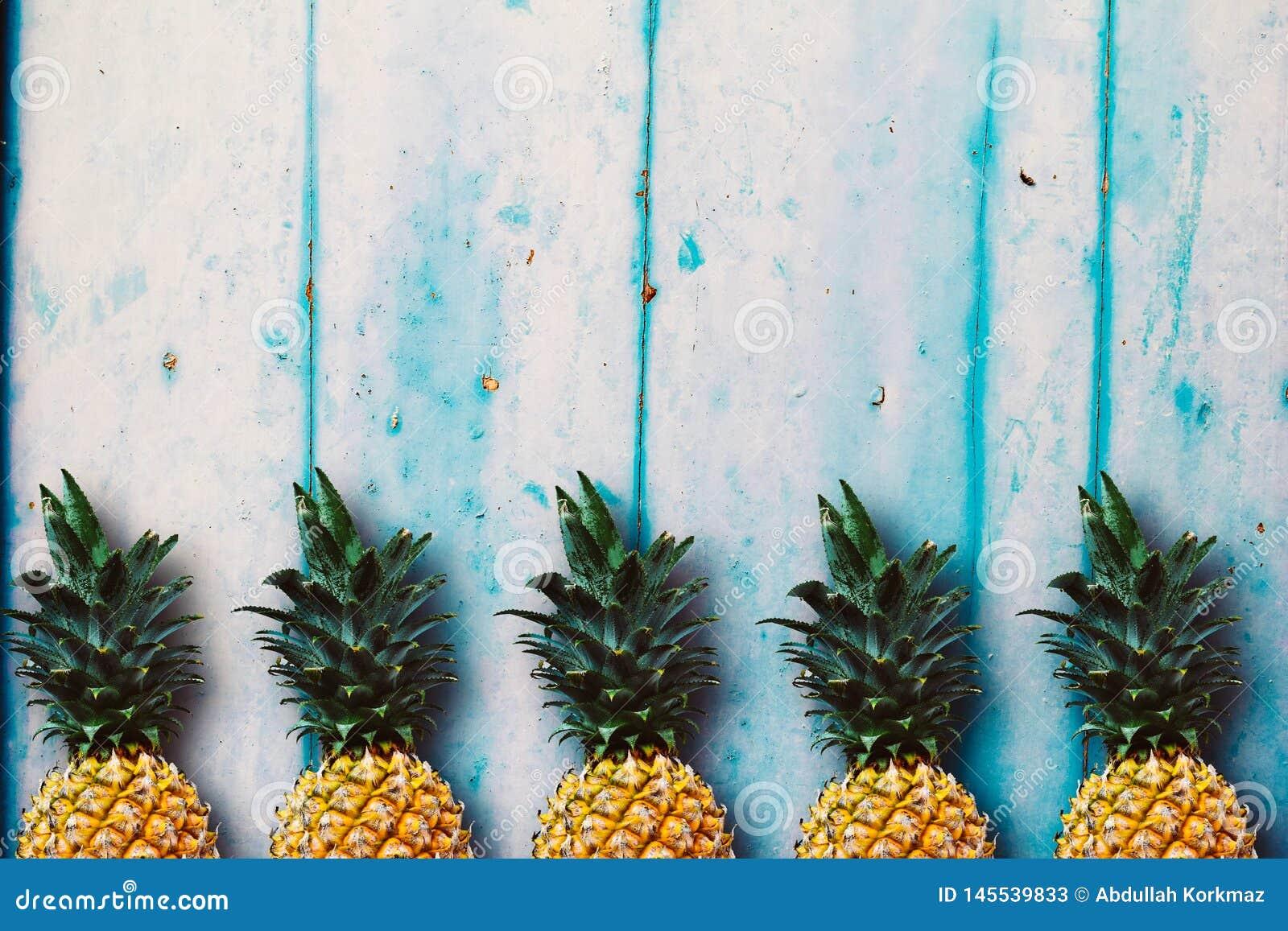 Зрелые ананасы над голубым деревянным столом