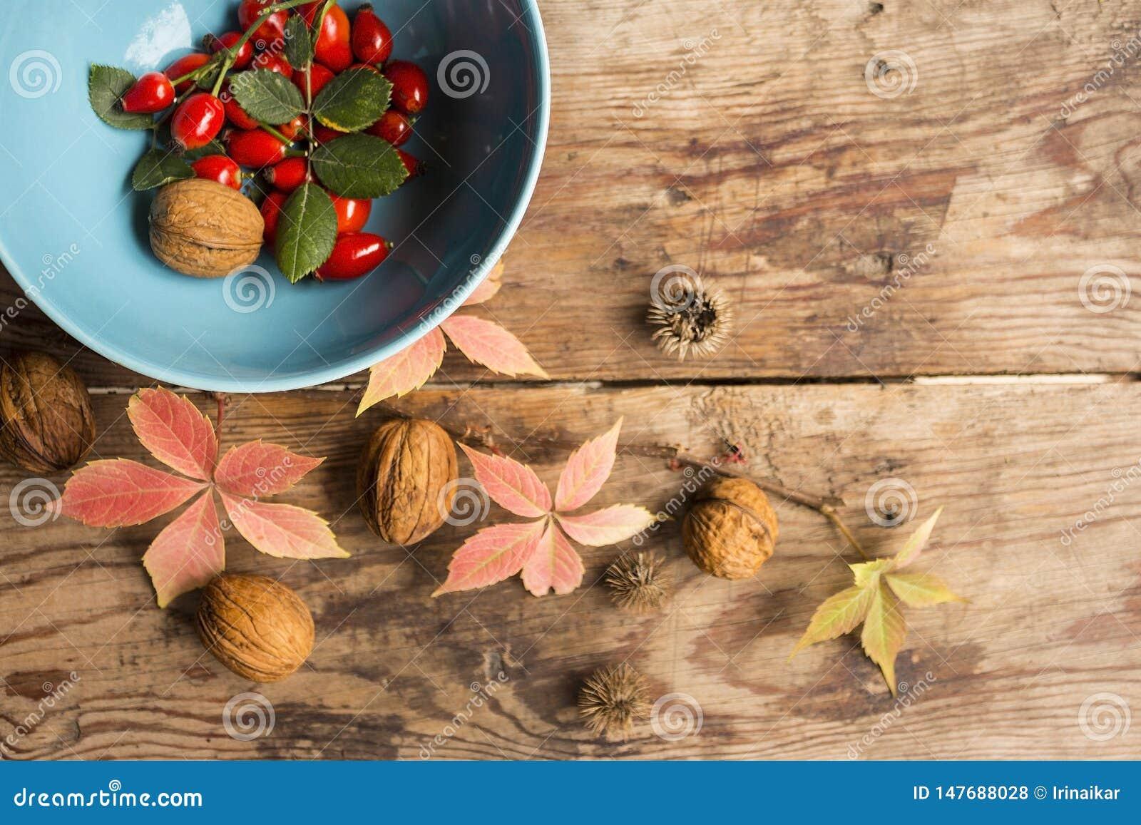 Зрелые красные плоды собак-Роза в голубой чашке с розовыми листьями, гайками на старом деревянном столе