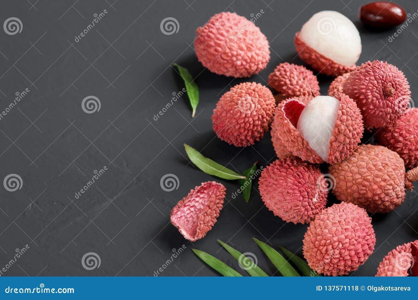 Зрелые красные ягоды lychee плоско кладут на черную предпосылку скопируйте космос