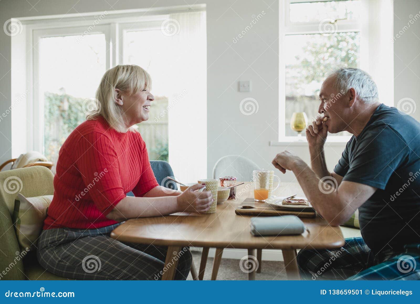 Зрелые пары наслаждаясь завтраком дома