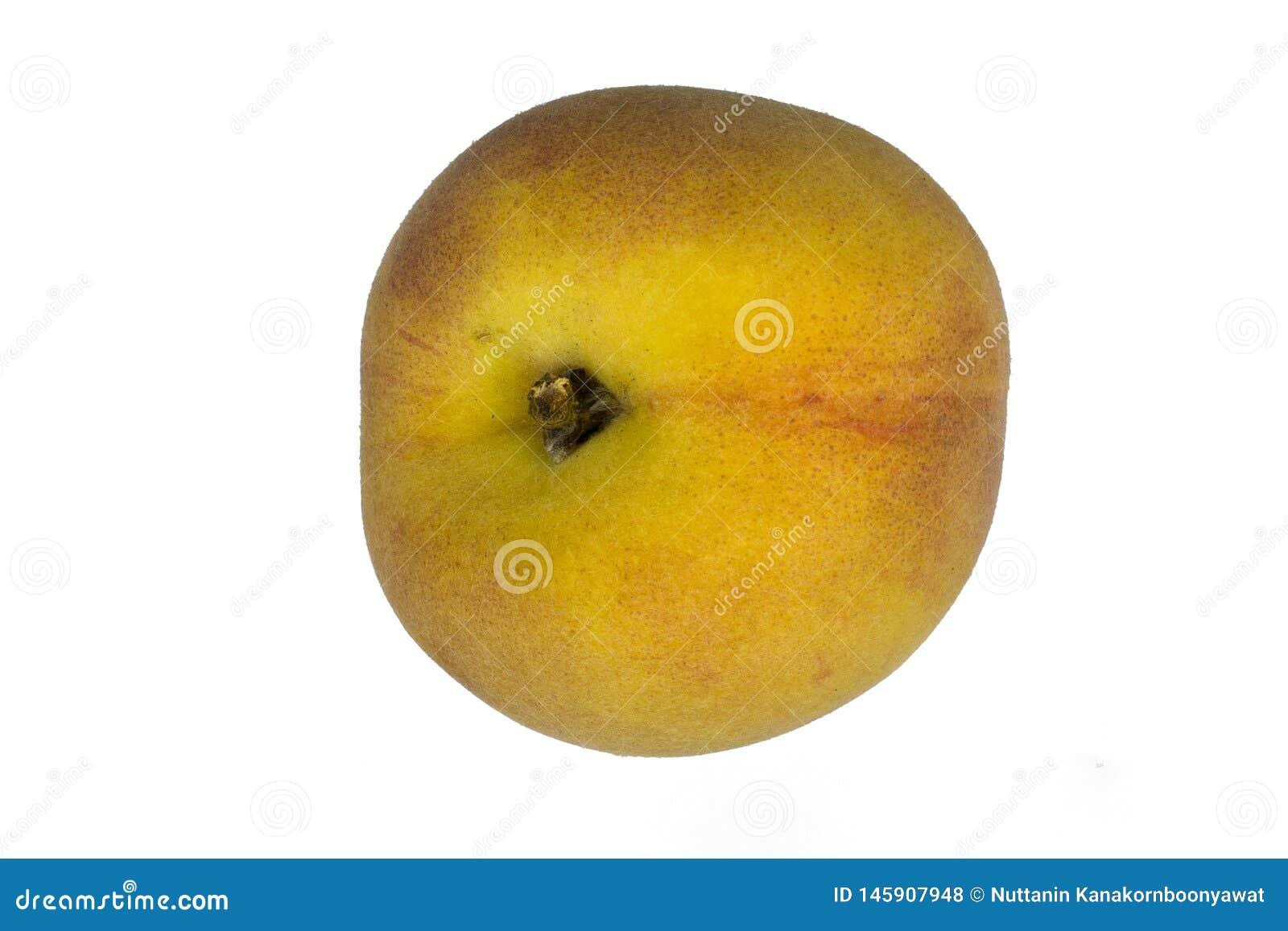 Зрелый плод персика изолированный на глубине поля белой предпосылки полной