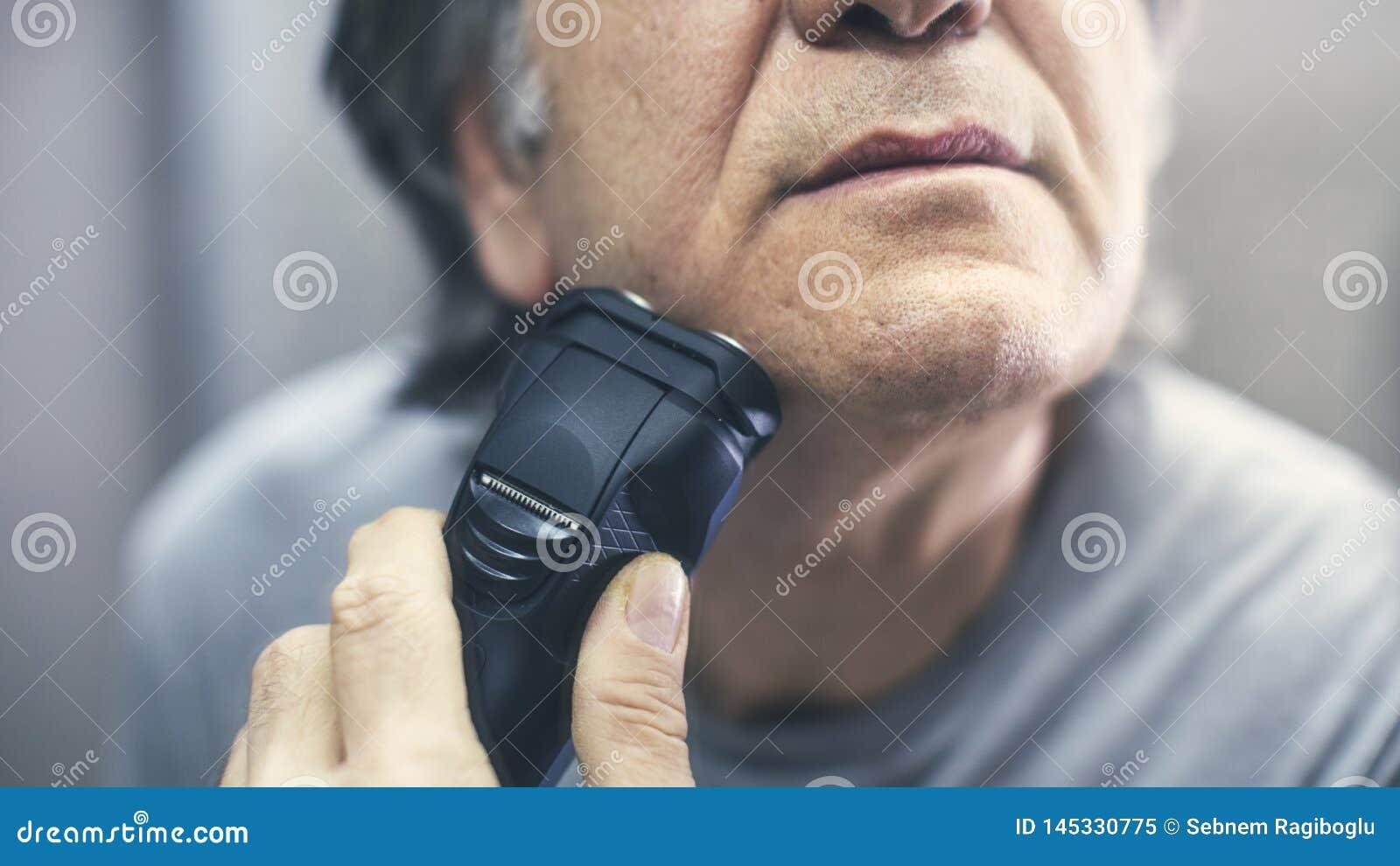 Зрелый человек брея перед зеркалом