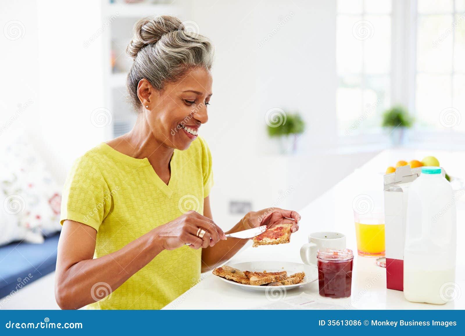 Зрелая женщина есть варенье завтрака распространяя на здравице