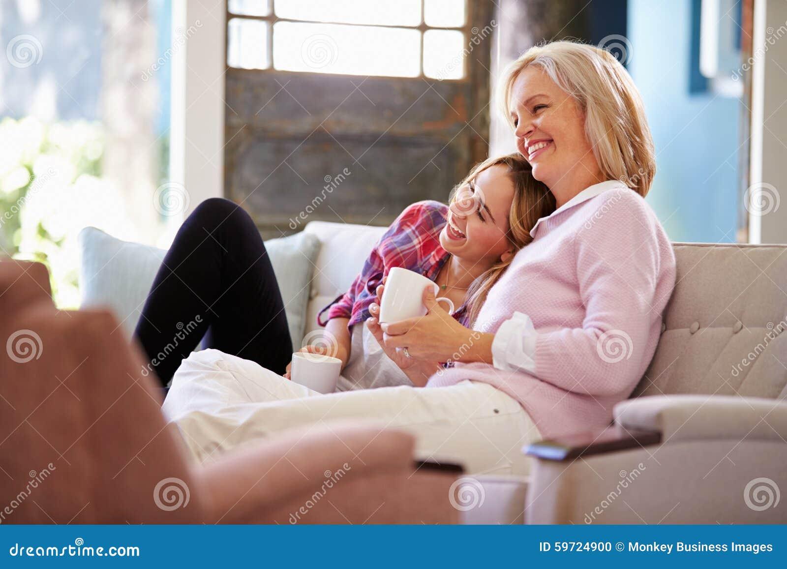 Зрелая мать при взрослая дочь смотря ТВ дома