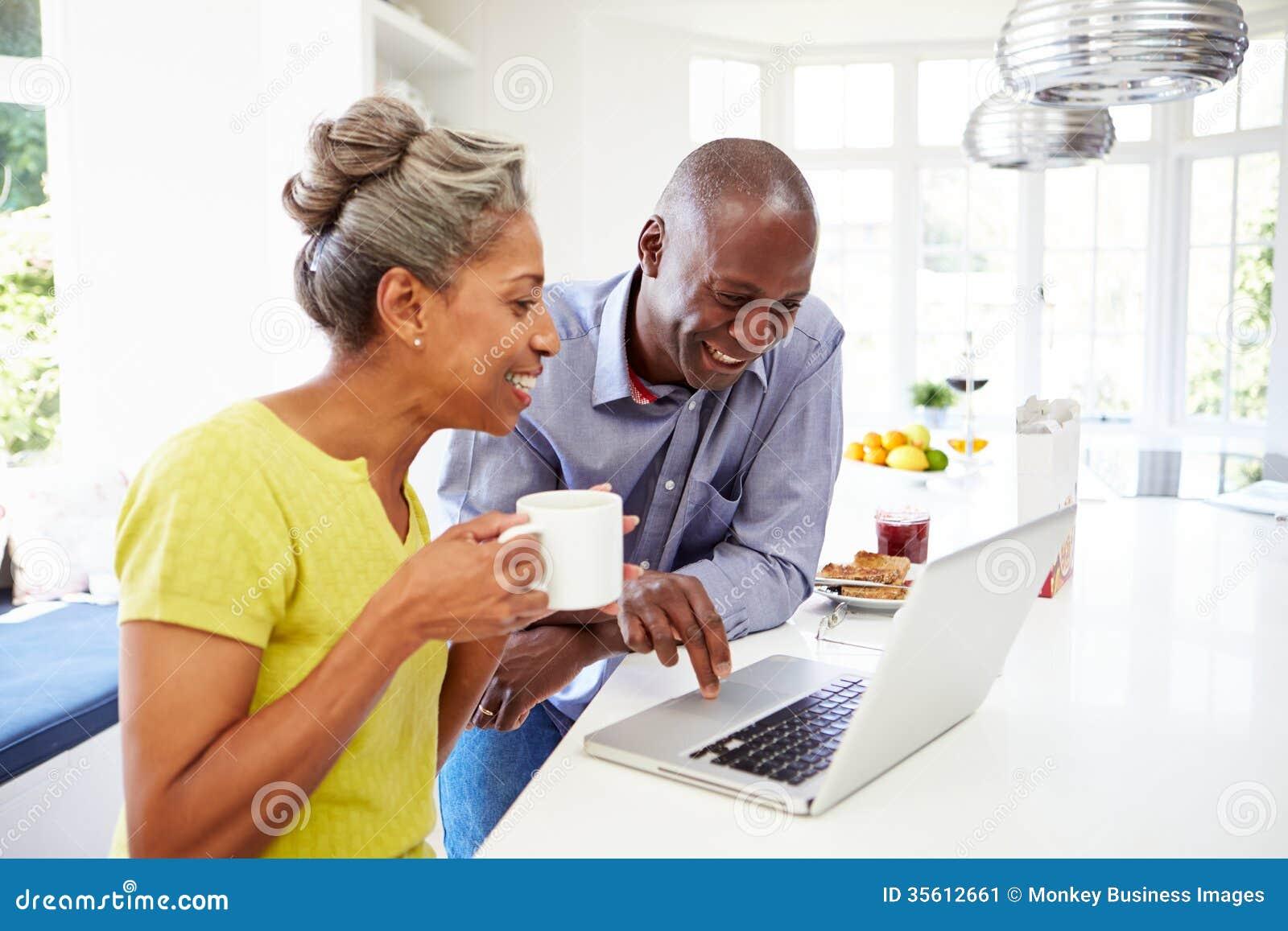 Зрелые Афро-американские пары используя компьтер-книжку на Bre