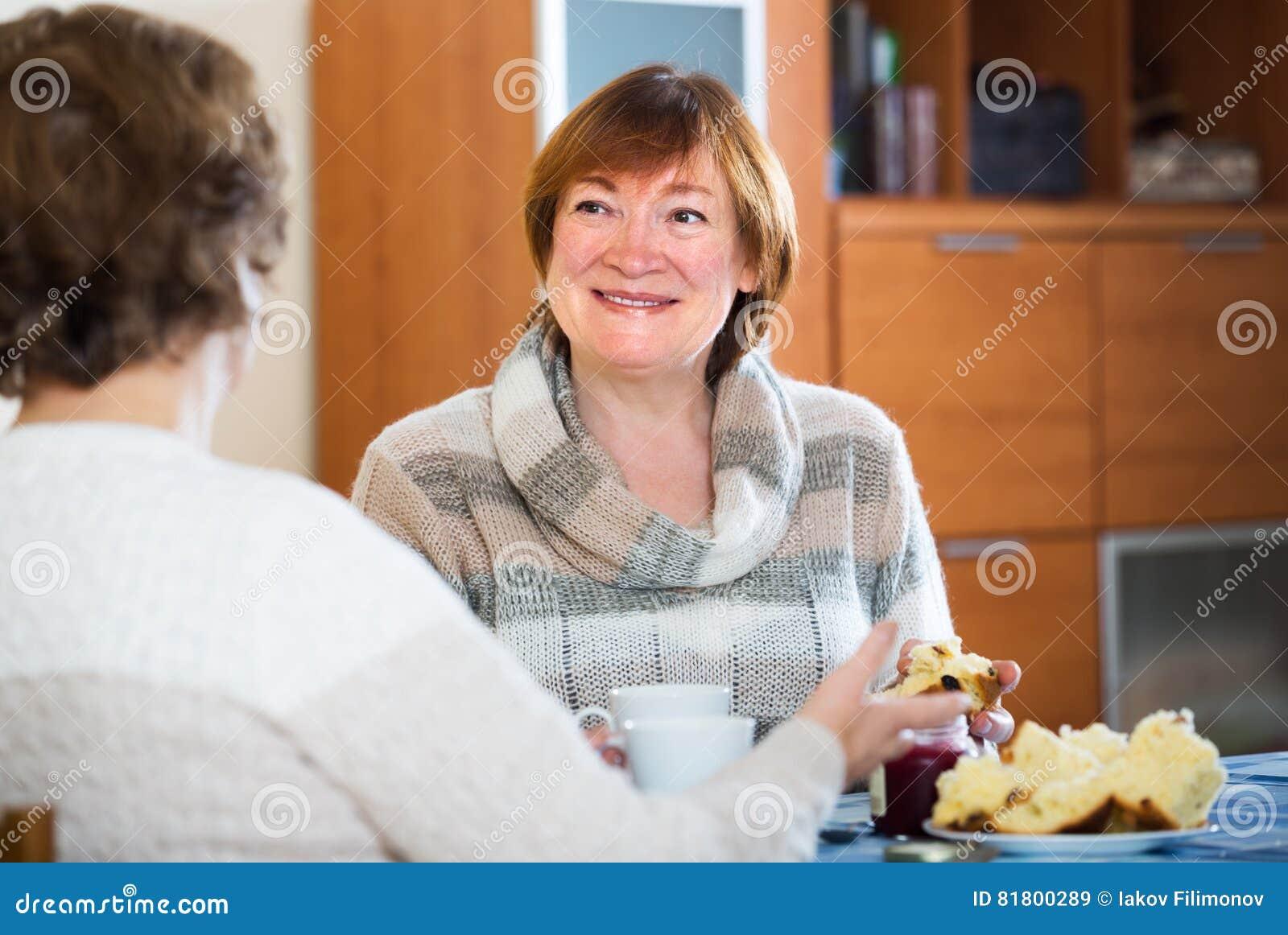 Зрелые женщины сидя и беседуя