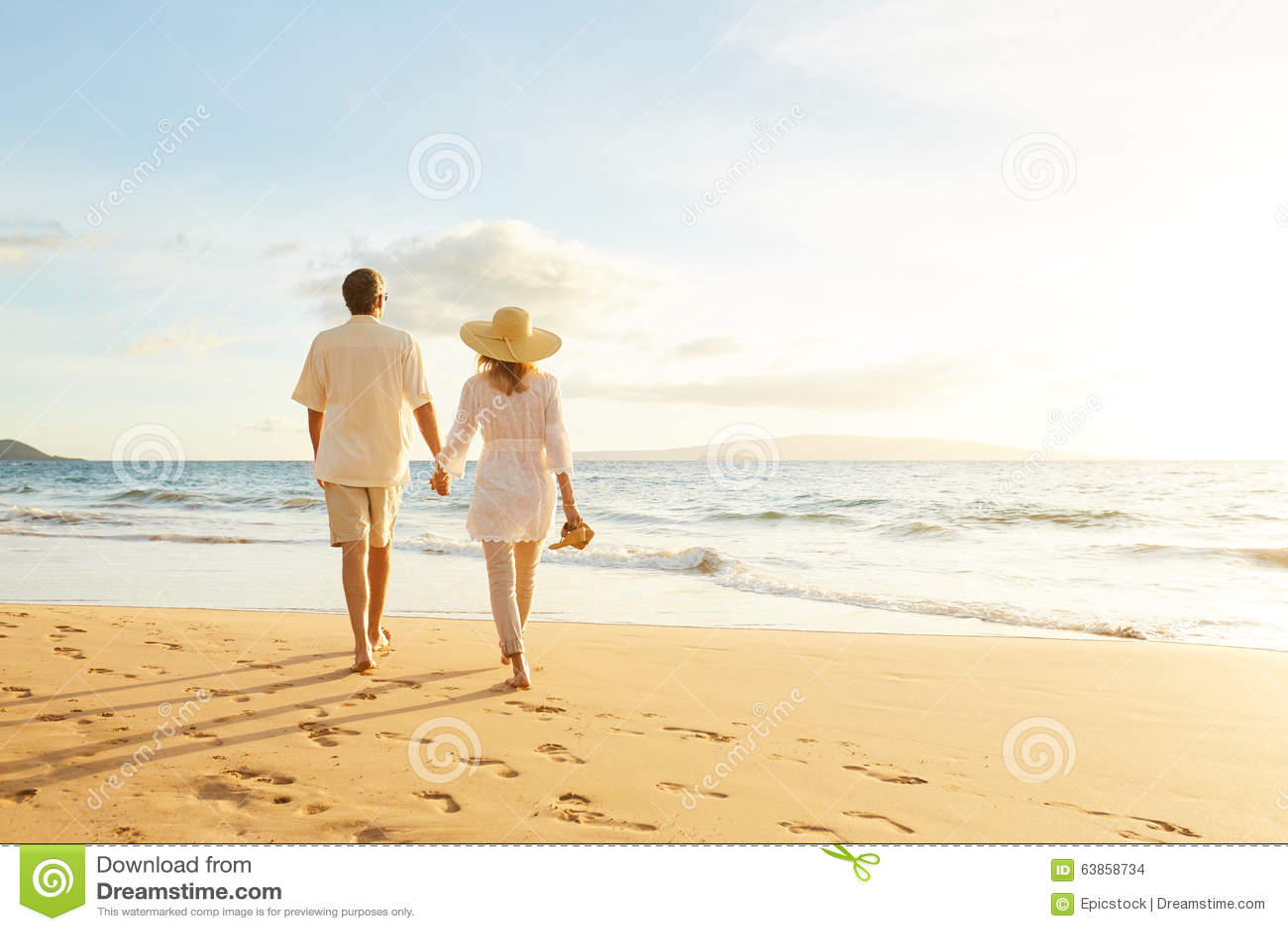 Зрелые пары идя на пляж на заходе солнца